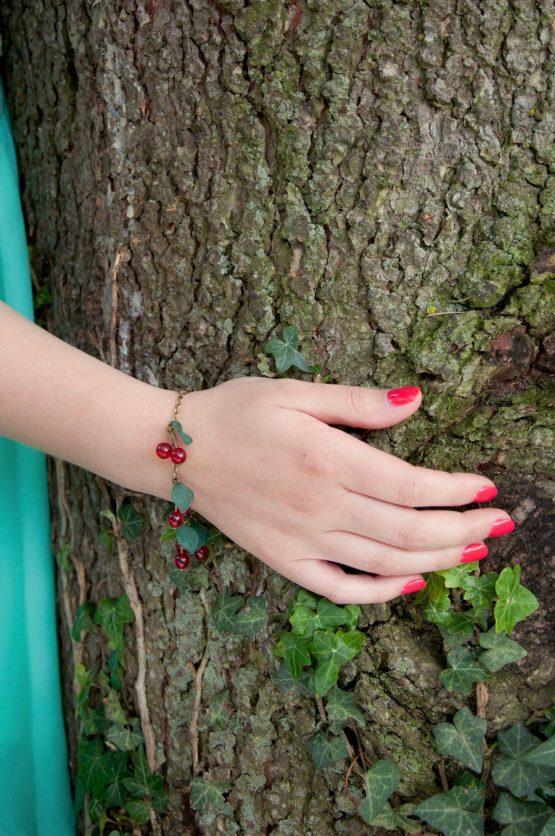 bracelet cerises en métal couleur bronze laiton et des perles de verre rouges porté pour Annamorfoz